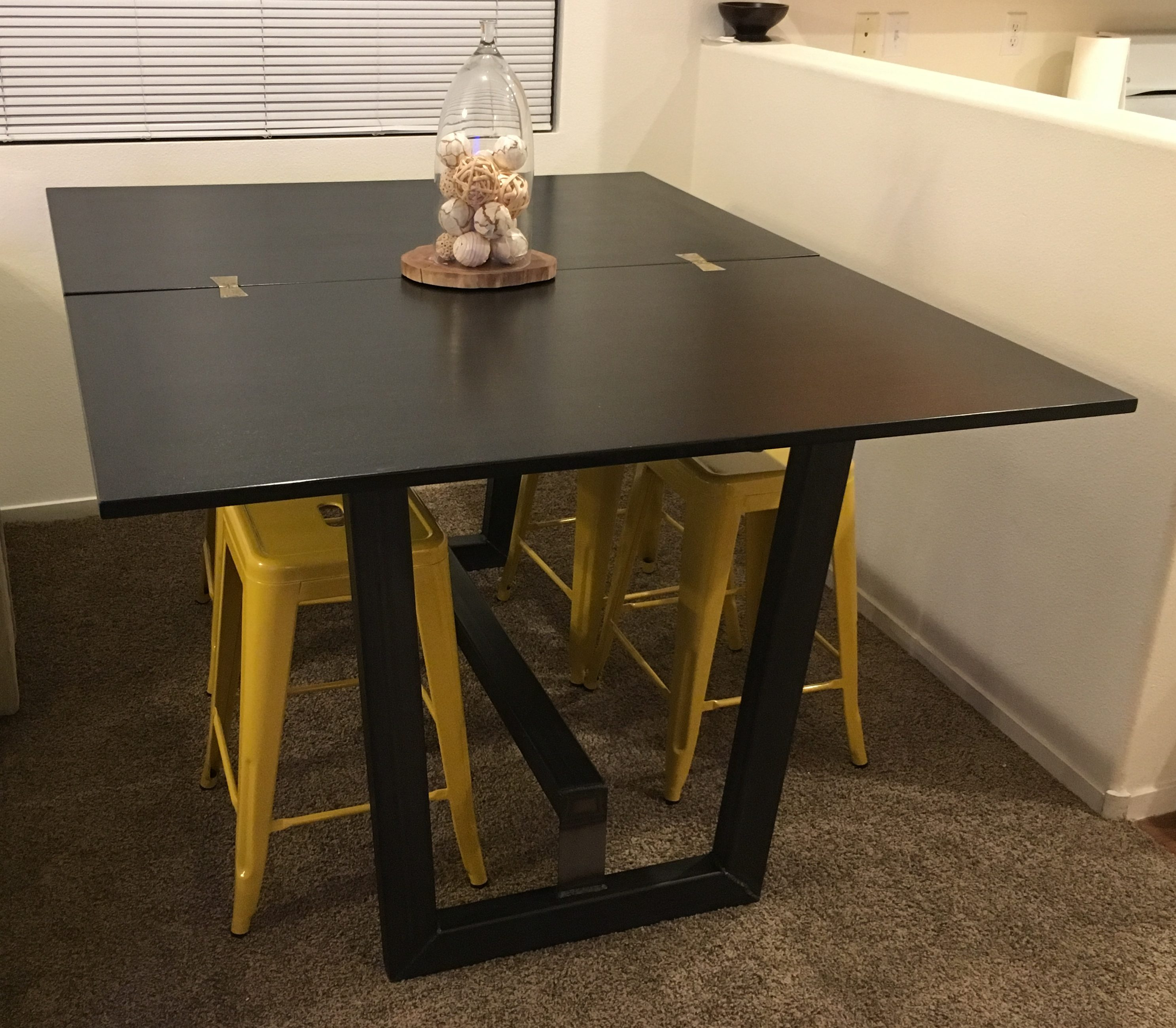 Dining table unfolded to be a larger table on a custom metal base.